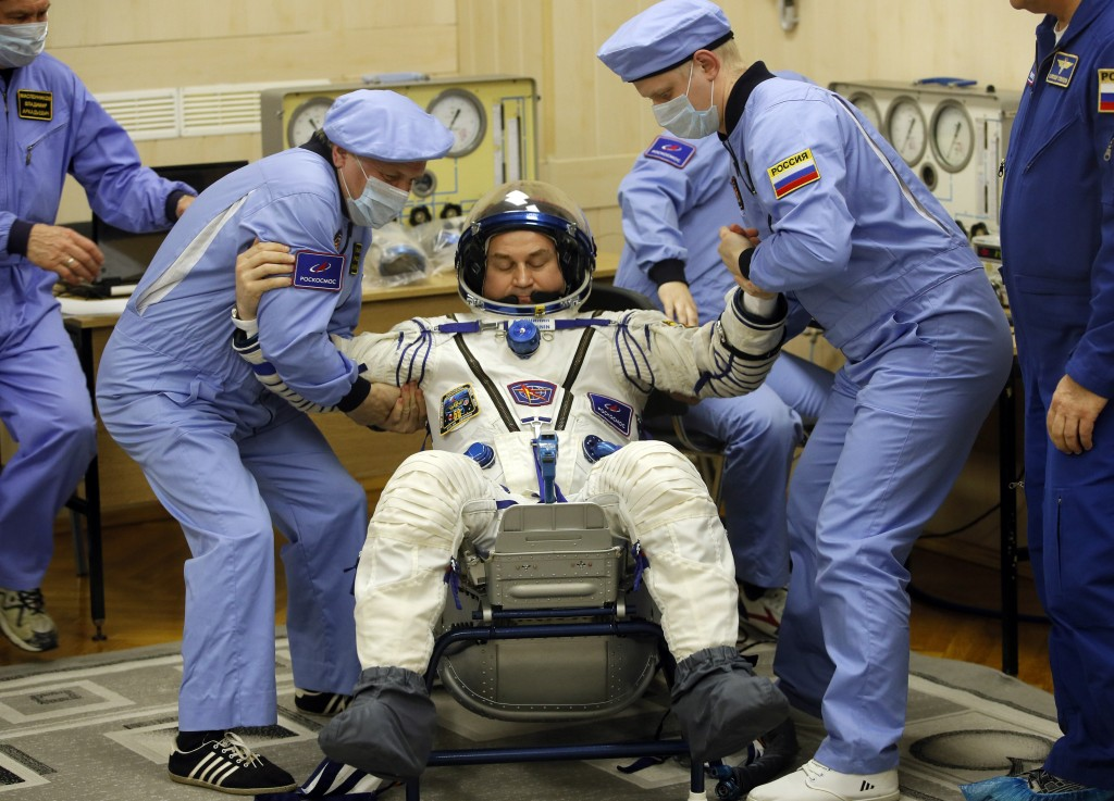 Russian Space Agency experts help Russian cosmonaut Alexey Ovchinin, member of the main crew of the expedition to the International Space Station (ISS