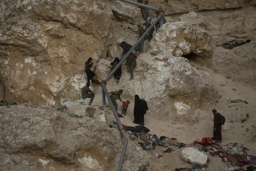 People who left the besieged Islamic State-held village of Baghouz, Syria, scramble up a rocky hillside to be checked by U.S-backed Syrian Democratic