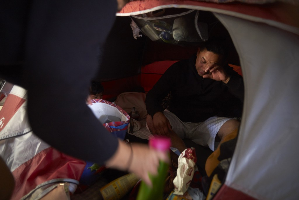 In this March 5, 2019, image, Juan Carlos Perla reacts as he and his wife, Ruth Aracely Monroy, left, searches for medicine in their tent for their 10