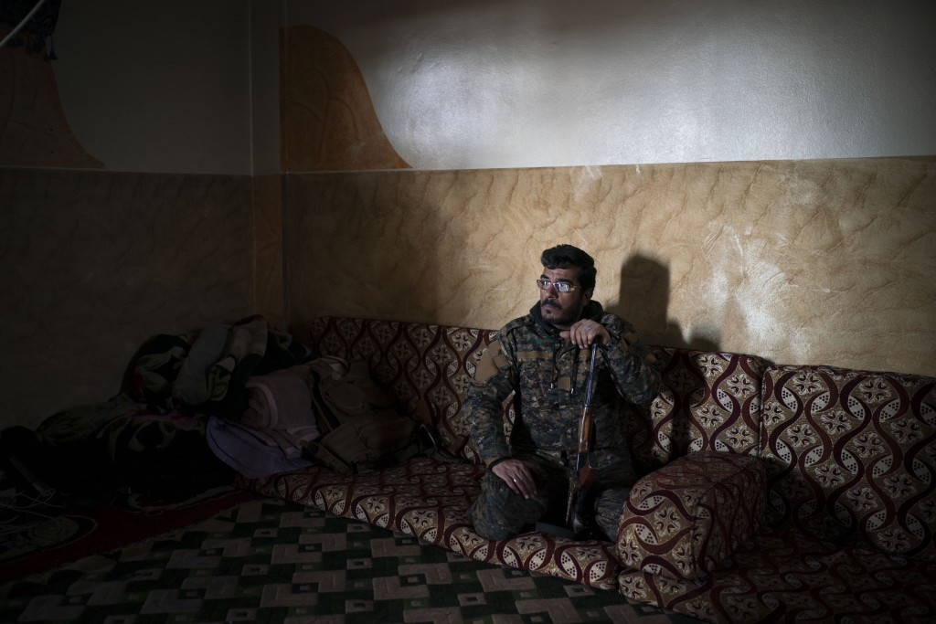 In this Feb. 18, 2019 photo, Dia Hassakeh, 45, a fighter in the Kurdish-led U.S-backed Syrian Democratic Forces, looks out of a building in Baghouz, S