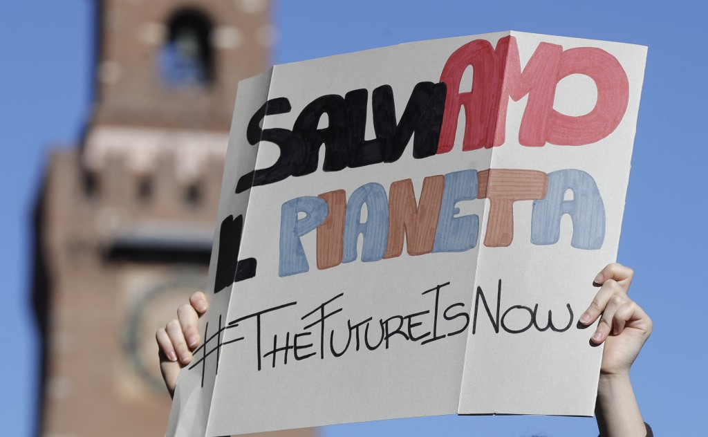 "A student holds up a sign with writing reading in Italian ""Lets save the planet"", during a demonstration outside the Castello Sforzesco castle, in Mil"