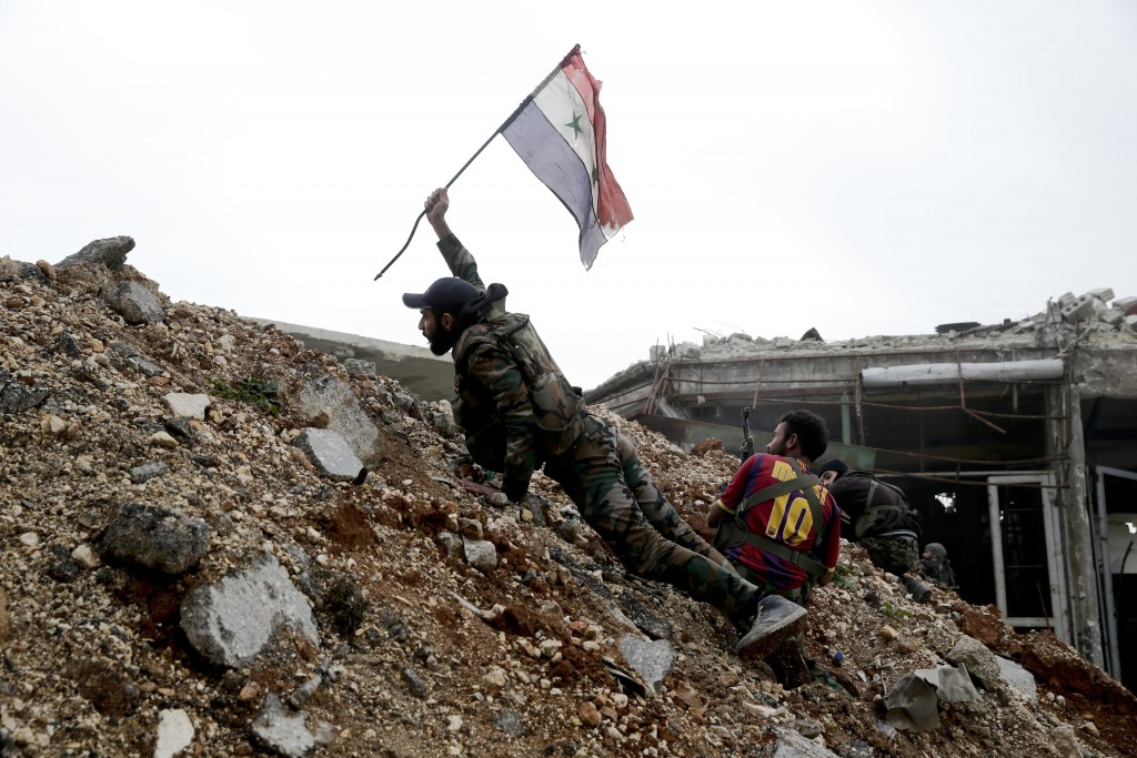 FILE - In this Dec. 5, 2016 file photo, a Syrian army soldier places a Syrian national flag during a battle with rebel fighters at the Ramouseh front
