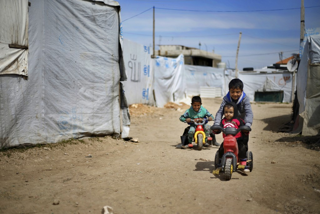 This Tuesday, March 12, 2019 photo, Syrian displaced children play outside their family tents at a Syrian refugee camp in the town of Bar Elias, in Le