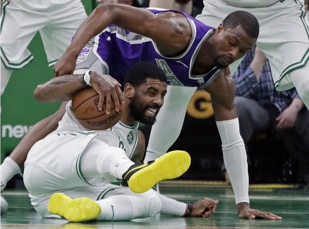 Boston Celtics guard Kyrie Irving, bottom, steals the ball from Sacramento Kings forward Harrison Barnes in the first half of an NBA basketball game, ...