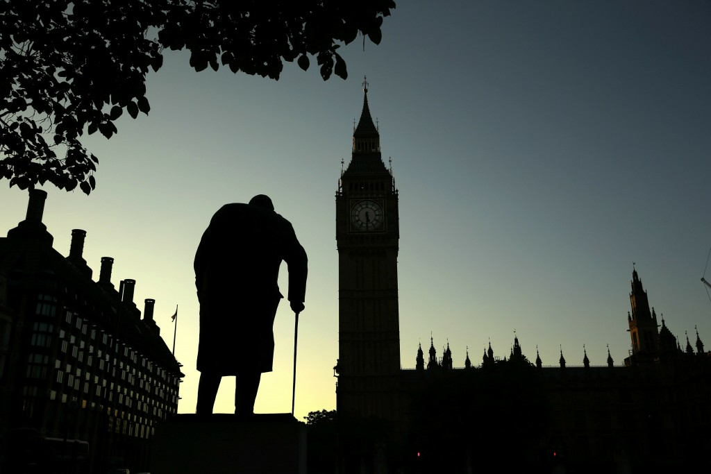 FILE - In this Friday, June 24, 2016 file photo file photo a statue of Winston Churchill is silhouetted against the Houses of Parliament and the early