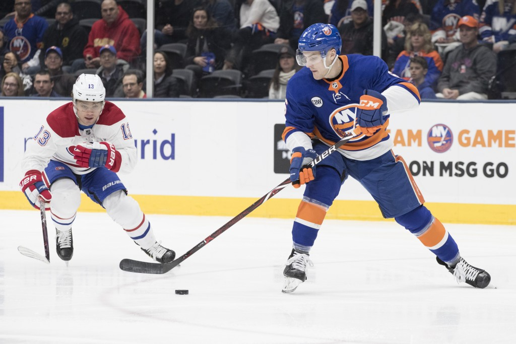 New York Islanders defenseman Ryan Pulock (6) skates against Montreal Canadiens center Max Domi (13) during the first period of an NHL hockey game, Th