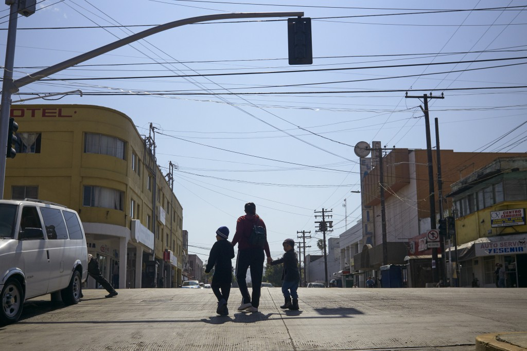 In this March 5, 2019, image, Ruth Aracely Monroy walks with her sons in Tijuana, Mexico. After requesting asylum in the United States, the family was