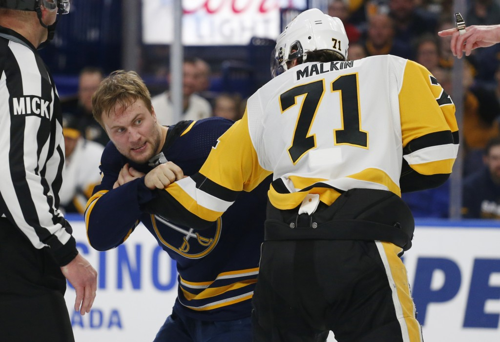 Buffalo Sabres forward John Larsson (22) and Pittsburgh Penguins forward Evgeni Malkin (81) fight during the third period of an NHL hockey game Thursd
