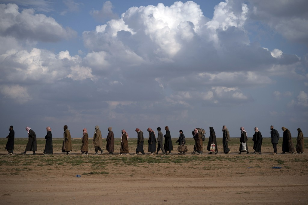 FILE - In this Feb. 22, 2019 file photo, men walk to be screened after being evacuated out of the last territory held by Islamic State militants, near