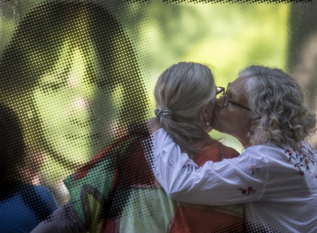 Photographed through a glass window that features a photograph, ESMA museum director Alejandra Naftal, right, kisses torture victim Ana Testa during t