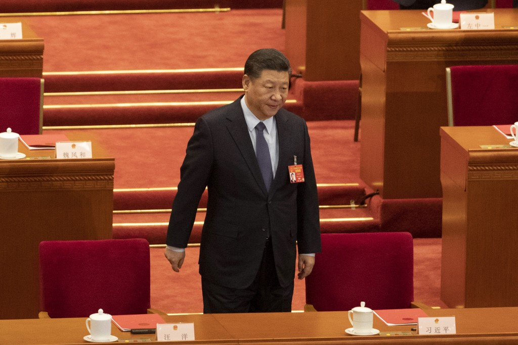 Chinese President Xi Jinping arrives for the closing session of the National People's Congress in Beijing's Great hall of the People on Friday, March