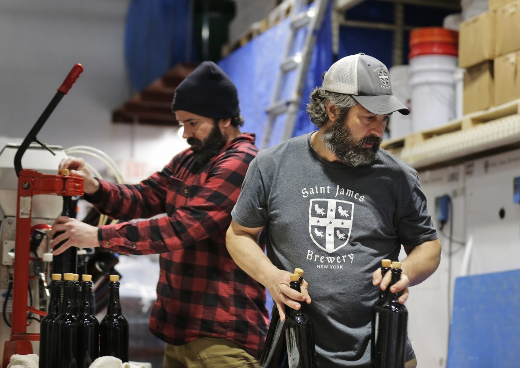 In this March 4, 2019, photo, brewery founder Jamie Adams, right, and John Condzella, left, bottle a batch of their Dubbel beer at the St. James Brewe