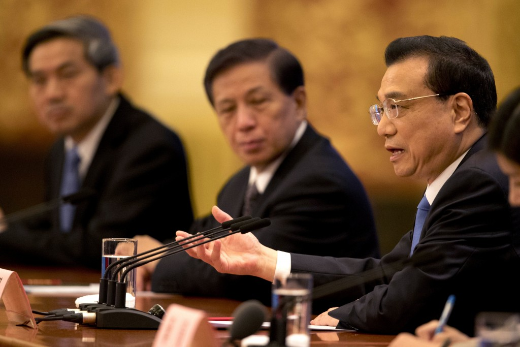Chinese Premier Li Keqiang, right, speaks during a press conference held after the closing session of China's National People's Congress (NPC) at the