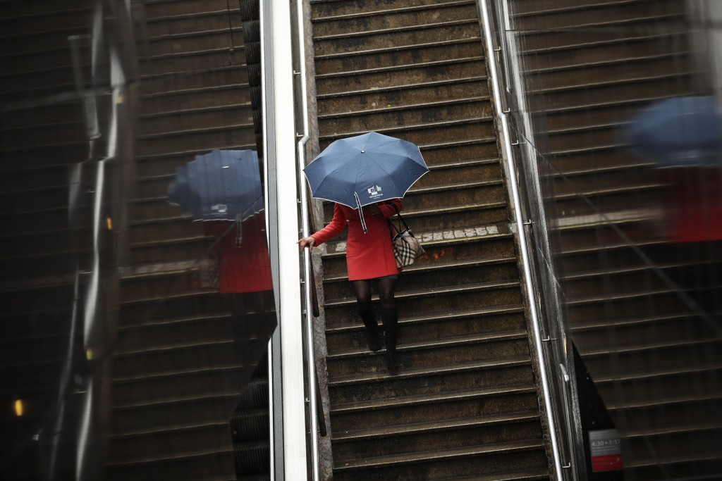 A woman shelters against the rain with un umbrella with the logo of the European Commission in Brussels, Thursday, March 14, 2019. Britons in Brussels