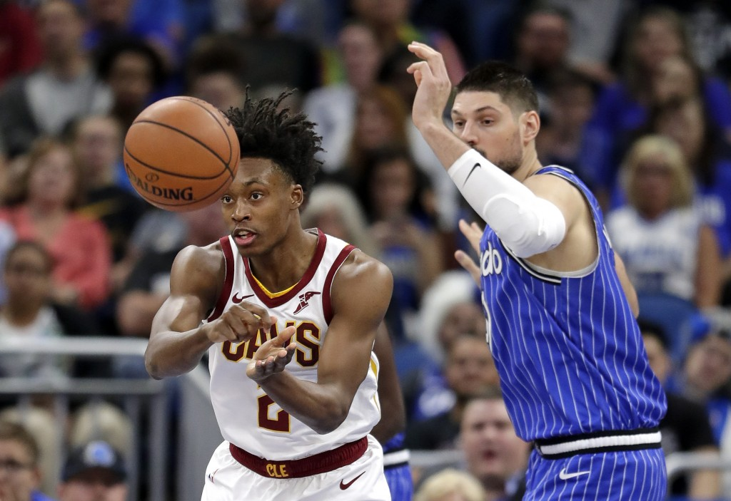 Cleveland Cavaliers' Collin Sexton, left, passes the ball around Orlando Magic's Nikola Vucevic during the first half of an NBA basketball game, Thurs
