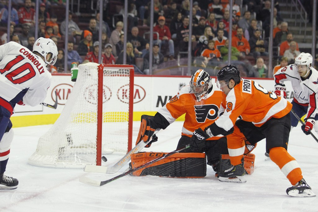Washington Capitals' Brett Connolly, left, scores past Philadelphia Flyers goalie Carter Hart, center, and Ivan Provorov, right, during the first peri