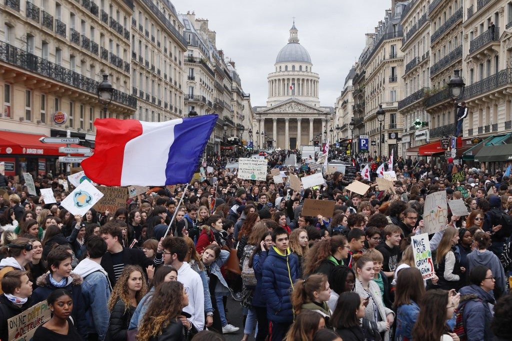 High school students demonstrate near the Pantheon monument, seen in background, one carrying the French flag, Friday, March 15, 2019 in Paris. Studen