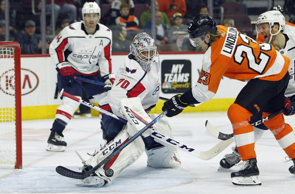 Washington Capitals' Braden Holtby kicks away a shot by Philadelphia Flyers' Oskar Lindblom during the second period of an NHL hockey game Thursday, M