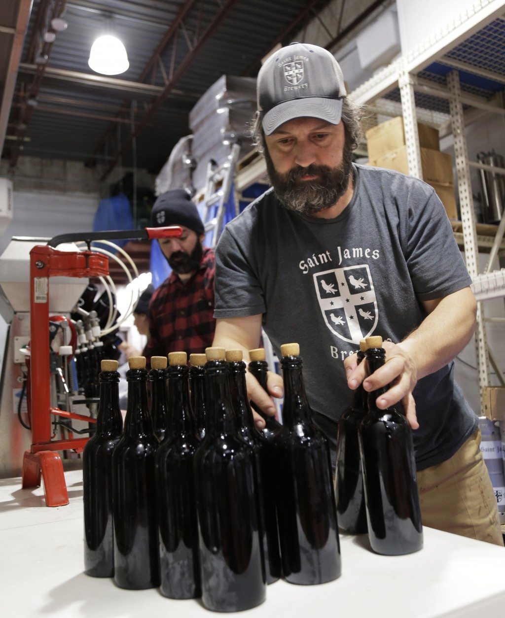 In this March 4, 2019, photo, brewery founder Jamie Adams, right, and John Condzella bottle a batch of their Dubbel beer at the St. James Brewery in H