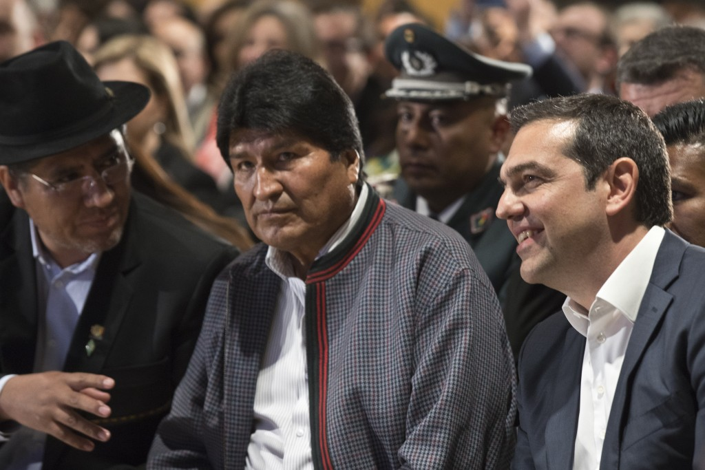 Bolivian President Evo Morales, center, and Greece's Prime Minister Alexis Tsipras, right, take part in a conference in Athens, Thursday, March 14, 20