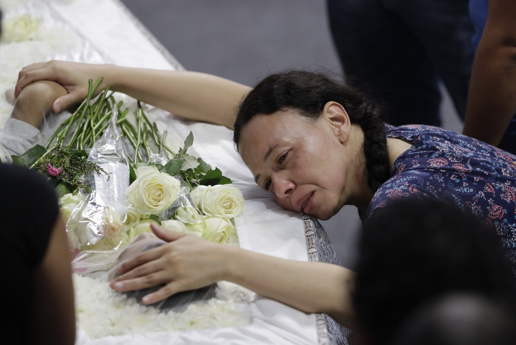 A relative mourns 15-year-old Caio Oliveira, a victim of a mass shooting at the Raul Brasil State School, in Suzano, Brazil, Thursday, March 14, 2019.