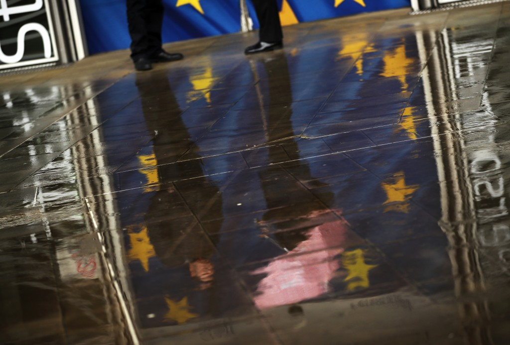 People and an European Union flags are reflected on the ground on a rainy day outside the European Commission headquarters in Brussels, Thursday, Marc