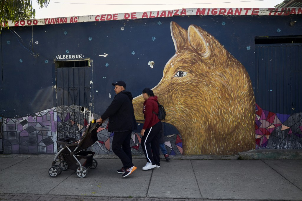 In this March 5, 2019, image, Juan Carlos Perla and Ruth Aracely Monroy leave a shelter for migrants in Tijuana, Mexico with their sons. After fleeing