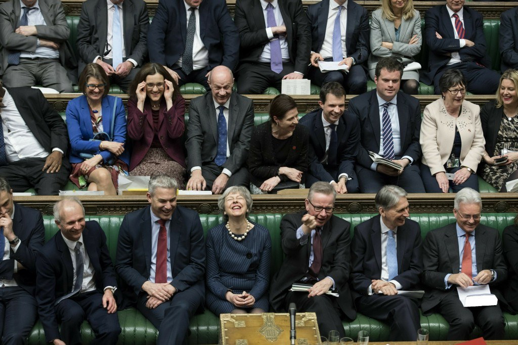 FILE - In this Thursday March 14, 2019 file handout photo provided by UK Parliament, Britain's Prime Minister Theresa May, first row centre, laughs du