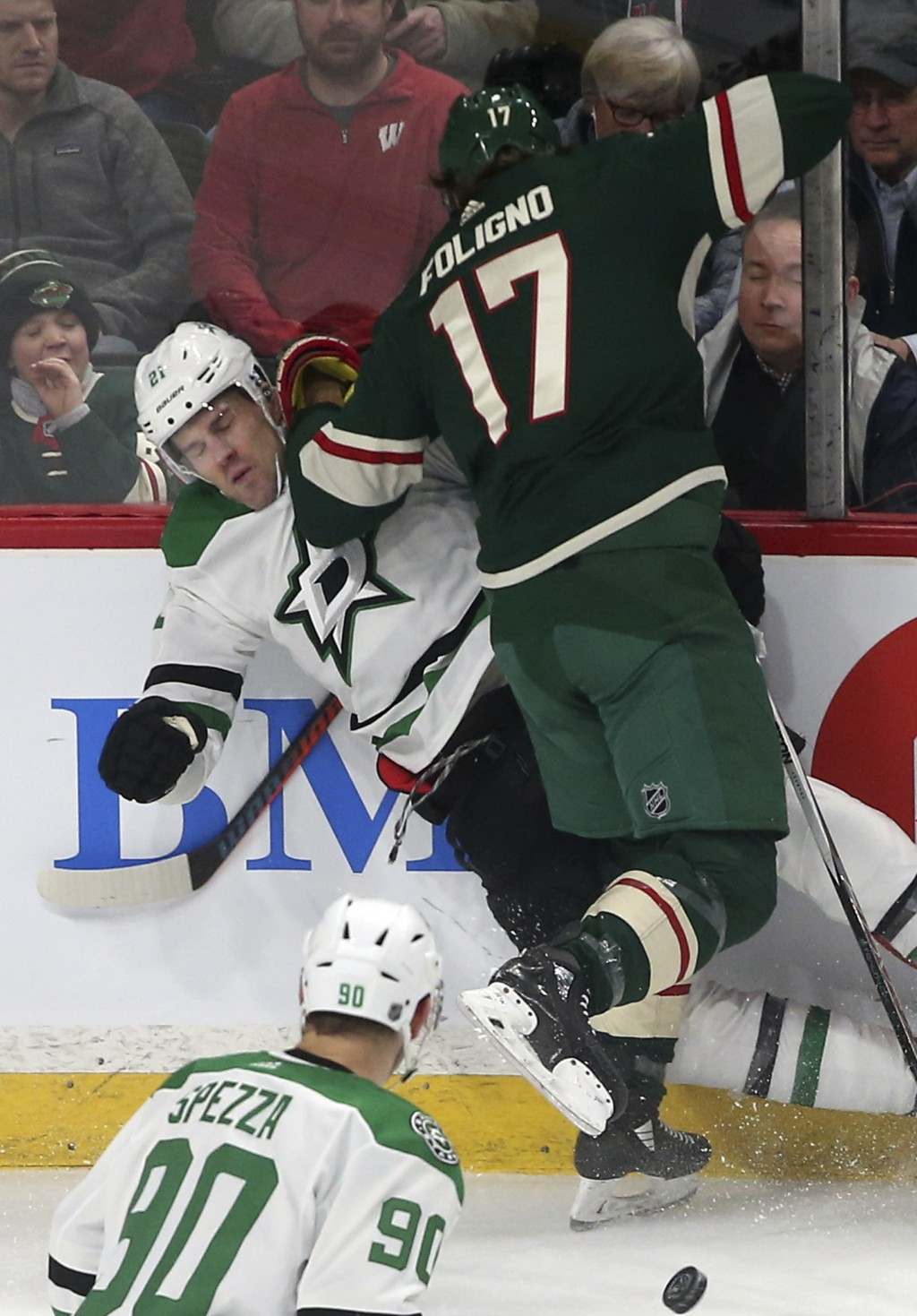 Dallas Stars' Ben Lovejoy, left, is checked into the boards by Minnesota Wild's Marcus Foligno in the first period of an NHL hockey game Thursday, Mar