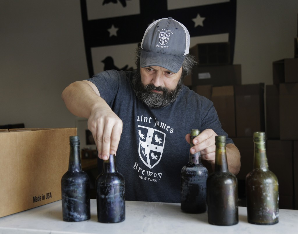 In this March 4, 2019, photo, Jamie Adams shows some intact beer bottles recovered from the shipwreck of the SS Oregon at his St. James Brewery in Hol