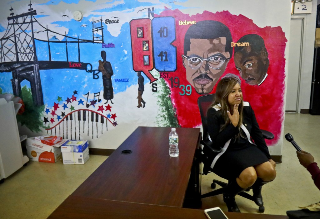 In this Wednesday, March 6, 2019 photo, Lynne Patton, HUD executive, sits near a wall mural during an interview at the Queensbridge Houses tenant asso