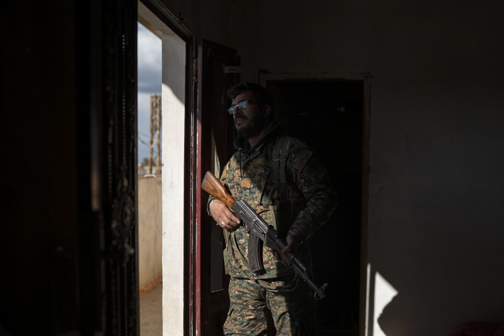 FILE - In this Feb. 17, 2019 file photo, Dia Hassakeh, 45, a fighter in the Kurdish-led U.S-backed Syrian Democratic Forces, looks out of a building i