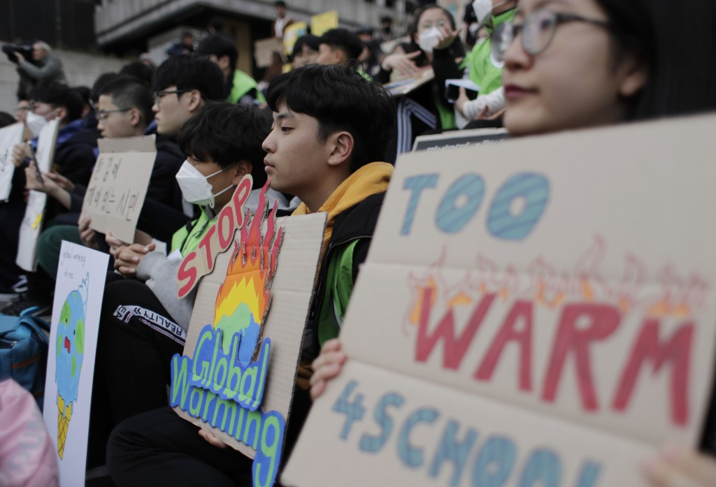 Students hold signs during a rally for global climate strike for future in Seoul, South Korea, Friday, March 15, 2019. About 150 students and other pr...
