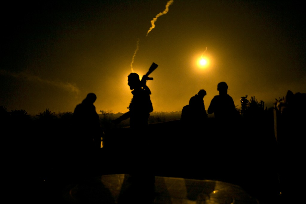 FILE - In this Tuesday, March 12, 2019 file photo, a U.S.-backed Syrian Democratic Forces (SDF) fighter watches illumination rounds light up Baghouz,