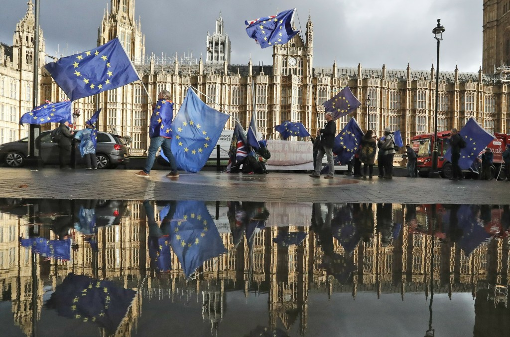 FILE - In this Monday, Dec. 3, 2018 file photo protestors are reflected in a puddle as they wave European flags to demonstrate against Brexit in front