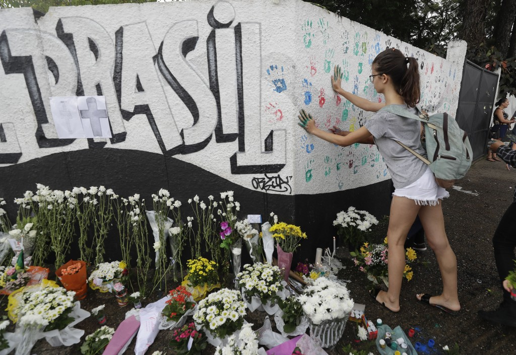 A student places her handprints on a wall at the Raul Brasil State School one day after a mass shooting, in Suzano, Brazil, Thursday, March 14, 2019.
