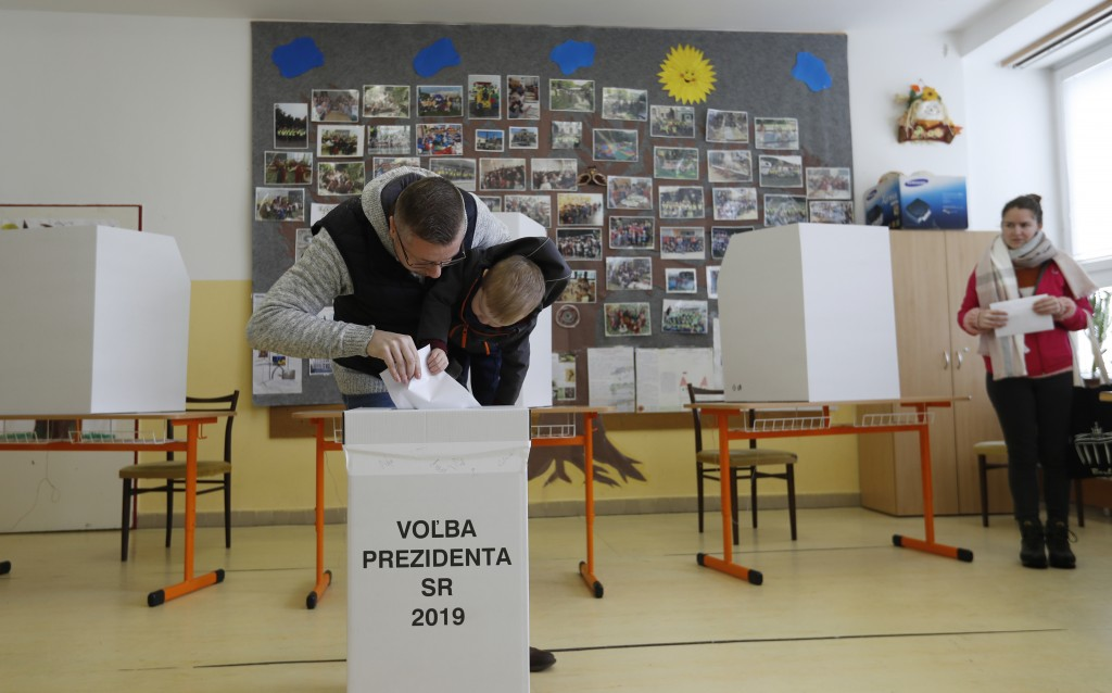 Father with his son cast a vote at a polling station during the first round of the presidential election in Bratislava, Slovakia, Saturday, March 16,
