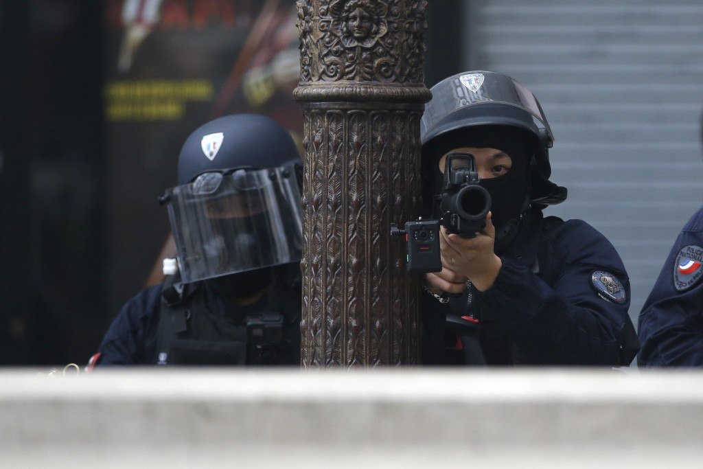 Riot police officers take position during a yellow vests demonstration on the Champs Elysees avenue Saturday, March 16, 2019 in Paris. French yellow v