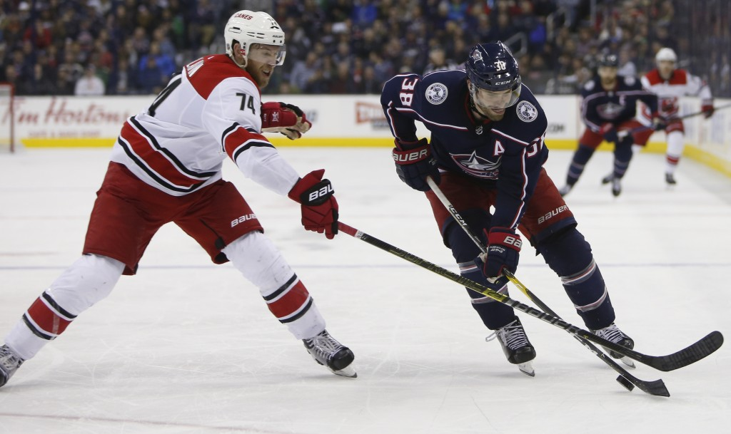 Columbus Blue Jackets' Boone Jenner, right, tries to skate past Carolina Hurricanes' Jaccob Slavin during the first period of an NHL hockey game Frida...