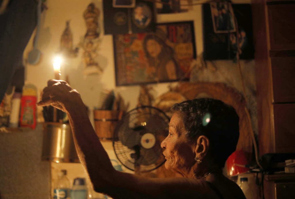 "72-year-old Elizabeth Guzman Espitia holds a candle in herwindowless room she calls her ""little cave"" during a blackout in the Santa Cruz of the East"