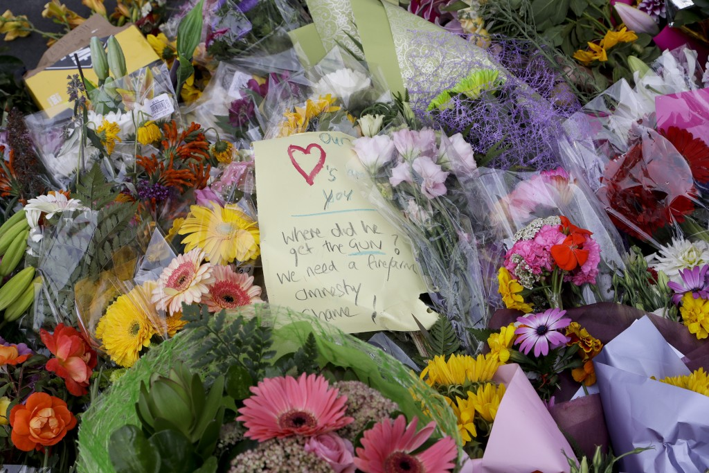 A handwritten message is placed at a collection of flowers left near the Masjid Al Noor mosque in Christchurch, New Zealand, Saturday, March 16, 2019,