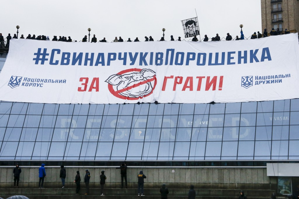 "Far-right demonstrators brandish flares as they display a large banner reading ""Poroshenko's pigs to jail"" during a rally against corruption in Kiev,"