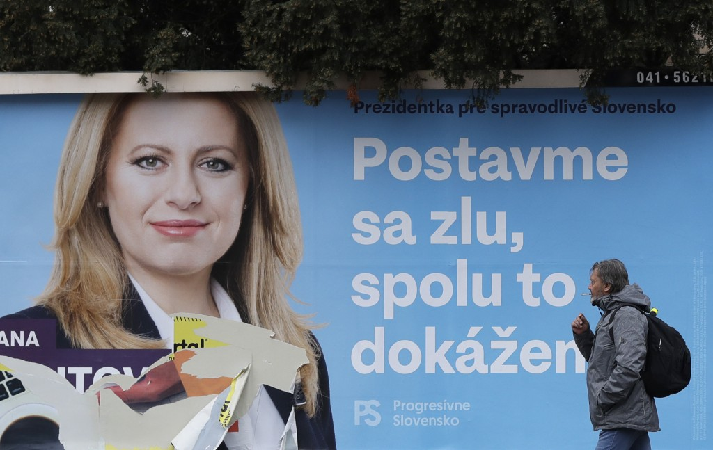 A man walks past a campaign poster for Zuzana Caputova in Bratislava, Slovakia, Friday, March 15, 2019. Caputova is one of the favorite candidates to