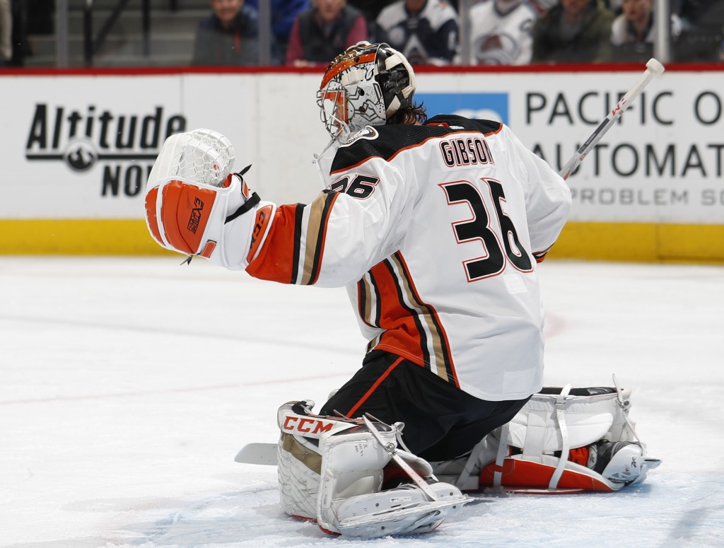 Anaheim Ducks goaltender John Gibson makes a glove save of a shot by the Colorado Avalanche during the first period of an NHL hockey game Friday, Marc...