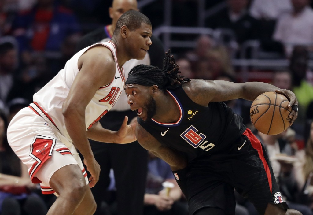 Los Angeles Clippers' Montrezl Harrell, right, is defended by Chicago Bulls' Cristiano Felicio during the first half of an NBA basketball game Friday,