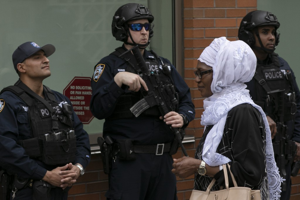 A woman leaves the Islamic Cultural Center of New York under increased police security following the shooting in New Zealand, Friday, March 15, 2019,