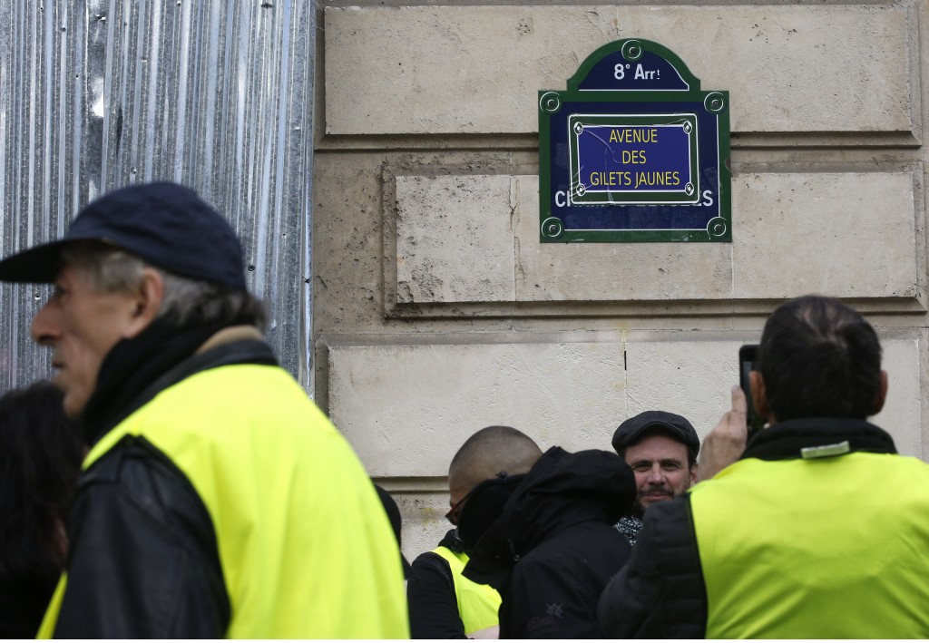"""A yellow vests protester takes a photograph of the the renamed Champs Elysees avenue as """"Yellow Vest avenue"""" during a demonstration Saturday, March 16"""