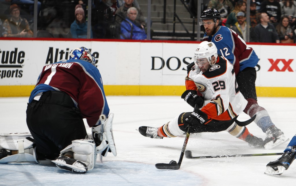 Anaheim Ducks center Adam Henrique, front right, tries to put a shot on Colorado Avalanche goaltender Semyon Varlamov, left, next to Avalance defensem