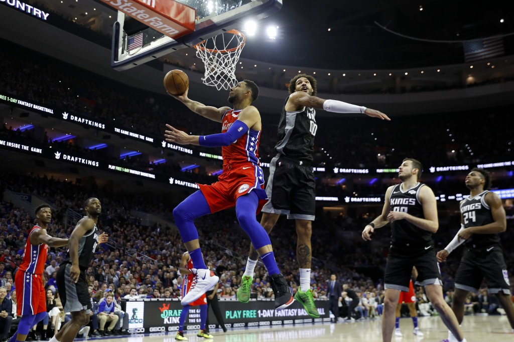 Philadelphia 76ers' Ben Simmons, left, goes up for a shot past Sacramento Kings' Willie Cauley-Stein during the first half of an NBA basketball game,