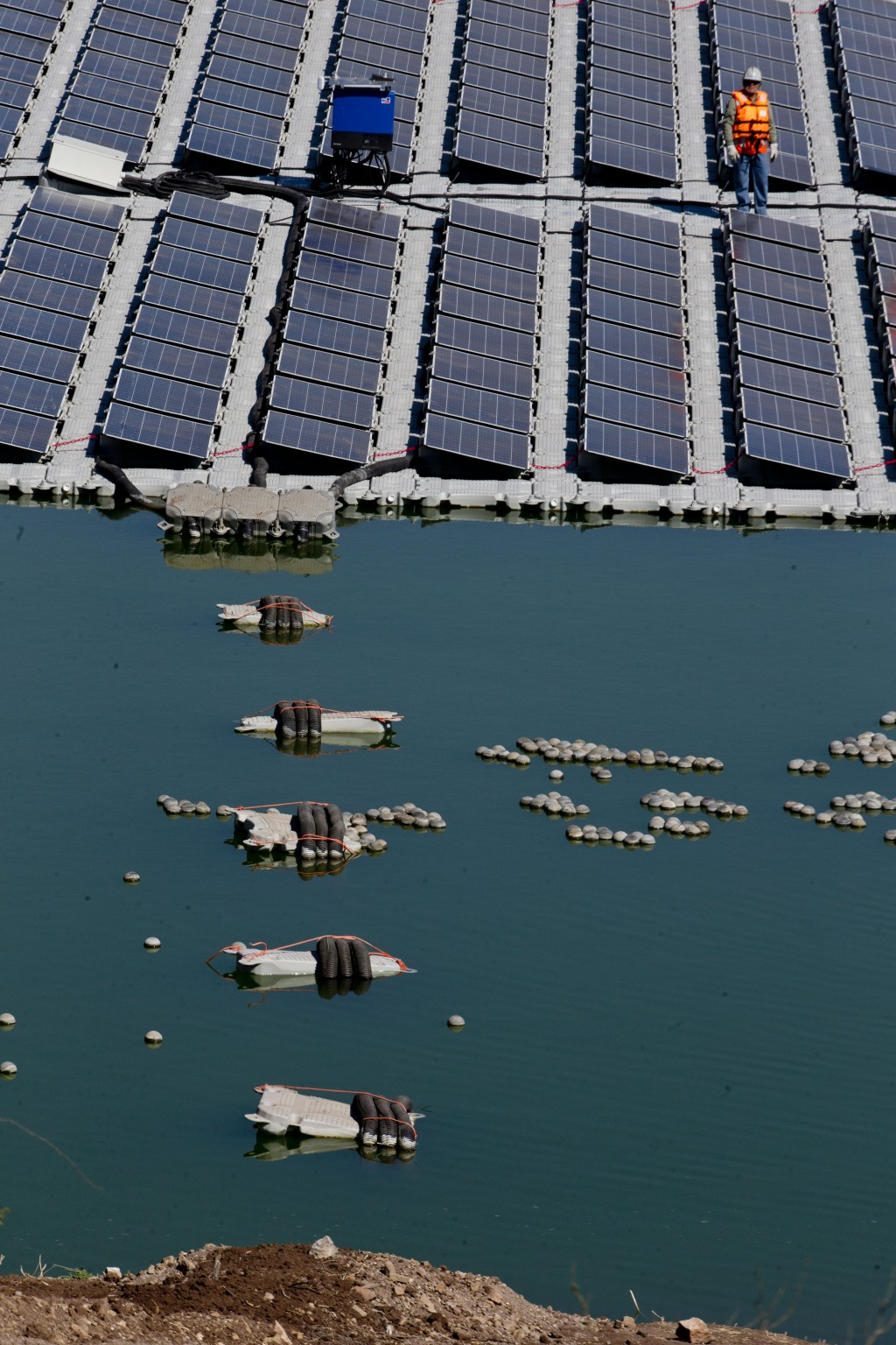 A worker stands on a floating island of solar panels at Los Bronces mine, about 65 kilometers (approximately 40 miles) from Santiago, Chile, Thursday,